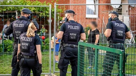 Polizisten sprechen mit Bewohnern, die hinter einem Bauzaun unter Quarantäne stehen