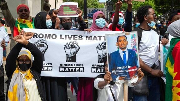 Demonstranten halten ein Bild des äthiopischen Sängers Hachalu Hundessa