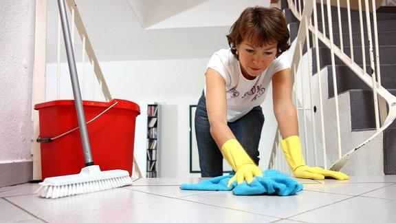Frau wischt die Fliesen des Fußbodens,
