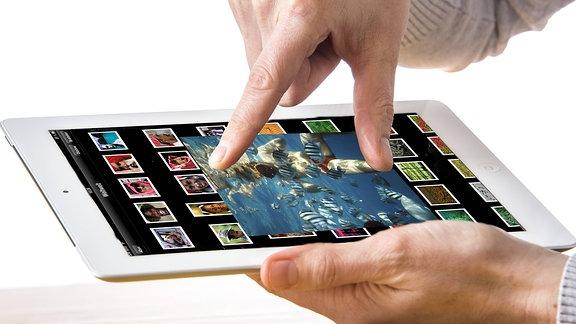 Eine Frau schaut sich auf einem Tablet Fotos an