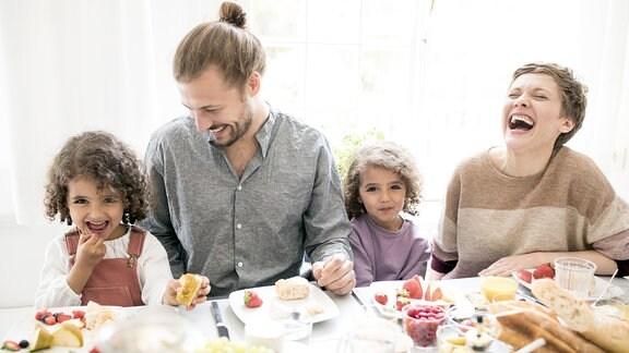 Fröhliche junge Familie am Frühstückstisch