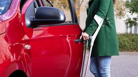 Eine Frau mit Krücken, die eine Tür eines Autos öffnet