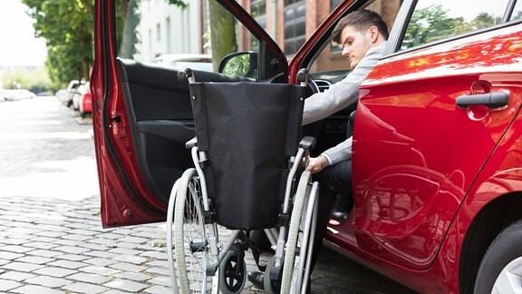 Ein Mann, der im Auto sitzt und seinen Rollstuhl faltet