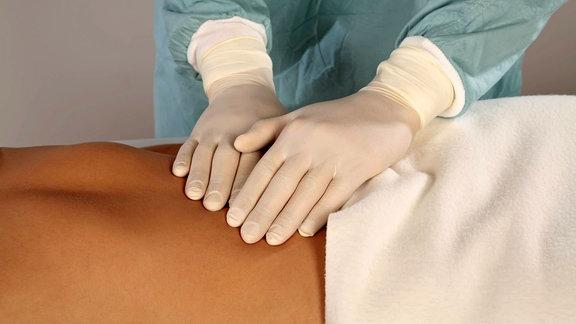 Arzt mit Gummihandschuhen tastet einer Patientin den Bauch ab.