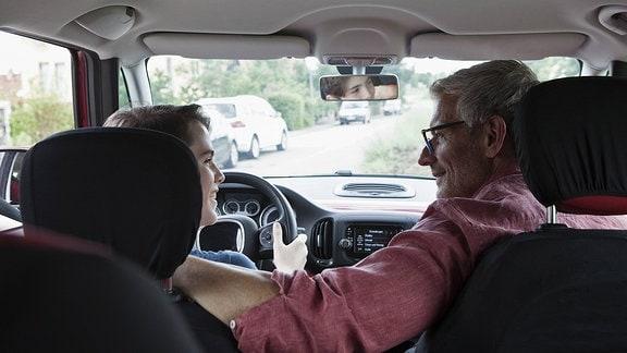 Ein Vater begleitet seinen Sohn beim Autofahren