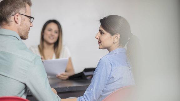 Junges Paar sitzt am Schreibtisch gegenüber einer Frau, die es berät.