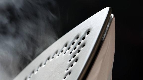 Wasserdampf entweicht aus den Bodenporen eines Dampfbügeleisens