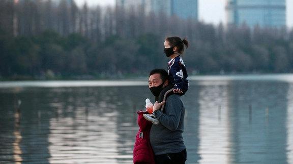 Ein Vater geht mit seiner Tochter am Ufer des Jiangsu-Flusses in der chinesischen Stadt Nanjing entlang. Bei tragen einen Mundschutz.