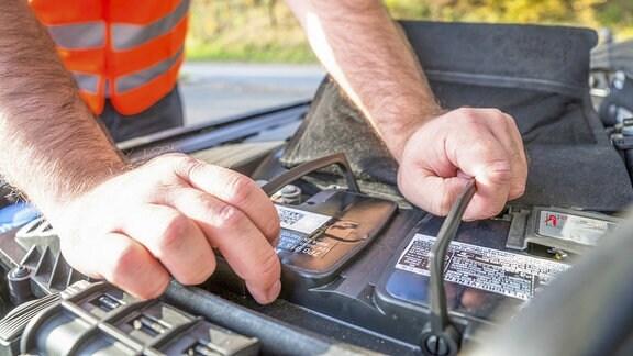 Ein Mann kontolliert eine Autobatterie.