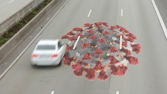 Symbolbild: Virus auf der Fahrbahn einer Autobahn mit fahrendem Auto
