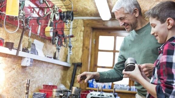 Vater und Sohn nehmen Autoteile in einer Werkstatt auseinander.