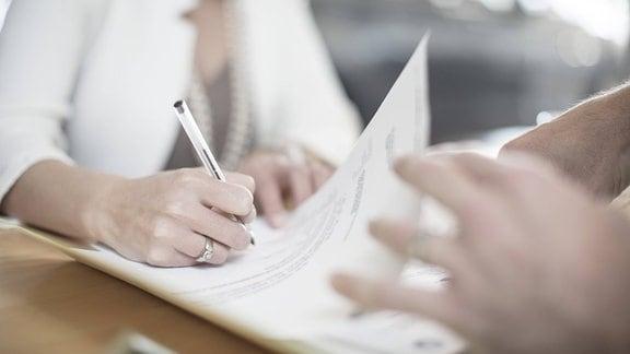 Eine Frau unterschreibt einen Vertrag.