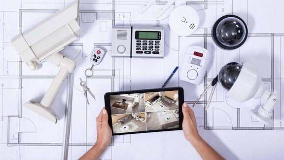 Auf einem Tablet-PC werden die Funktionen eines Smarthauses überwacht. Auf einem Grundriss liegen Kameras und andere Geräte.