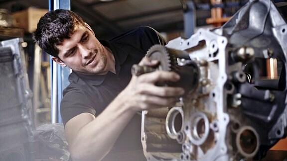 Ein Kfz-Mechaniker arbeitet an einem ausgebauten Motor.