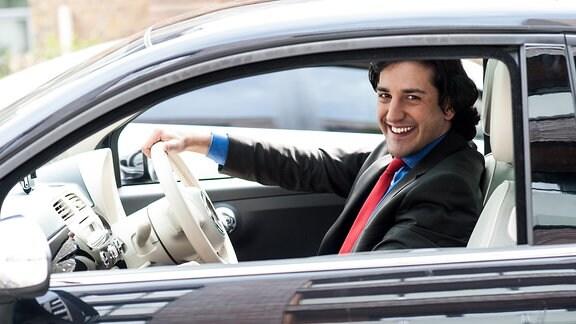 Ein Mann im Anzug sitzt hinter dem Lenkrad eines Autos und lacht in die Kamera