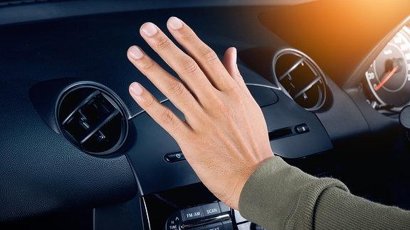 Eine männliche Hand fühlt den Luftzug einer Autoklimaanlage