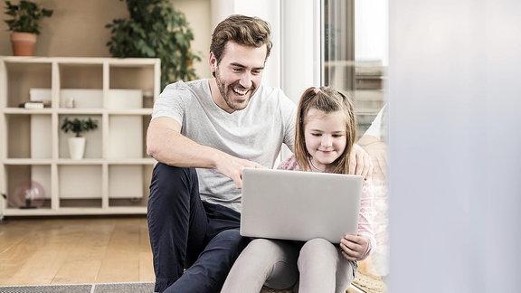 Junger Mann und kleines Mädchen, die zusammen im Internet surfen.