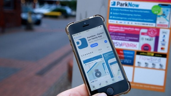 Hinweisschild für verschiedene Park Apps an einer Parkuhr.