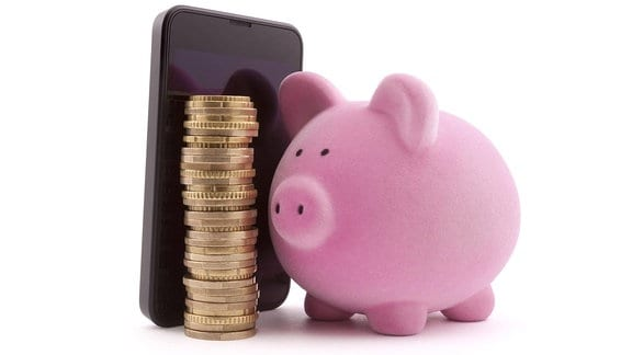 Ein Smartphone neben einem Stapel Münzen und einem Sparschwein