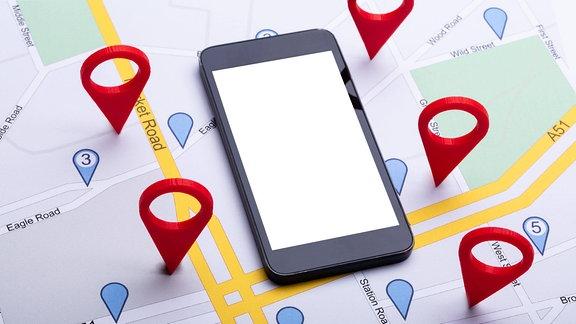 Ein Smartphone liegt auf einer Karte.