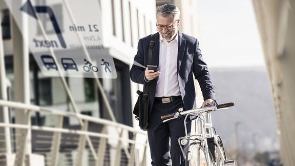 Geschäftsmann schiebt Fahrrad