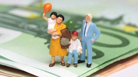 Modellfigurenfamilie mit Kindern steht auf einem Stapel aus Euro-Geldscheinen