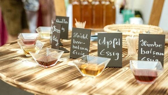 Verschiedene Essigsorten sind auf einem Holztisch zur Verkostung aufgestellt