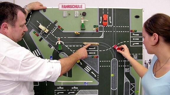 Ein Fahrlehrer übt mit einer Fahrschülerin an einer Karte die Verkehrsregeln.
