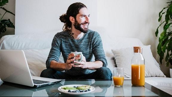 Lächelnder Mann mit Kaffeetasse, der weg schaut, während des Frühstücks auf dem Sofa zu Hause sitzt
