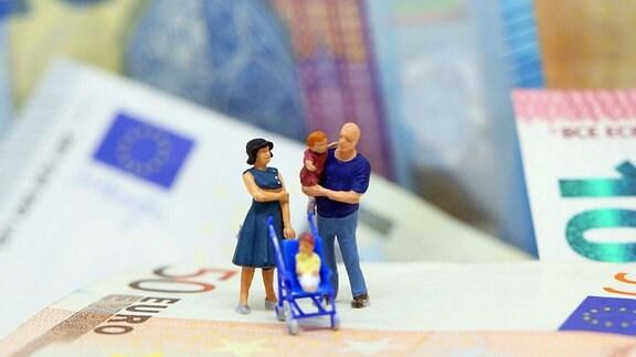 Themenbild - Plastikfiguren zeigen eine junge Familie mit Kinderwagen auf Euro Banknoten stehend.