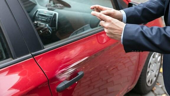 Eine Person fotografiert mit Smartphone ein beschädigtes Auto.