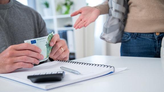 Hände halten einen hundert Euro Schein in der Hand.
