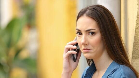 Eine Frau am Handy schaut betroffen