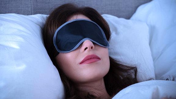 Frau liegt mit Schlafmaske im Bett