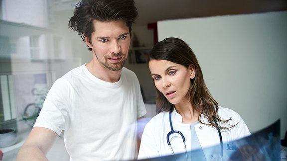 Ein Mann und eine Frau betrachten eine Röntgenaufnahme