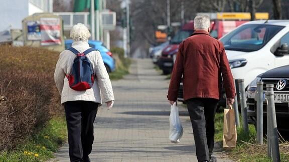 Ehepaar hält in Zeiten der Coronakrise auf der Strasse Abstand zueinander.