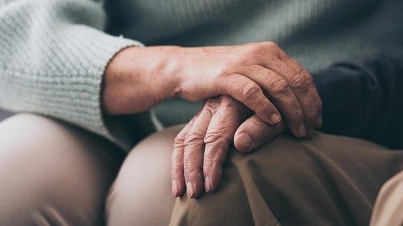 Eine Fau legt ihren Hand auf die eines Mannes