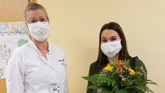 Zwei Frauen mit Mund-Nasen-Schutz stehen nebeneinander, eine hält einen Blumenstrauß