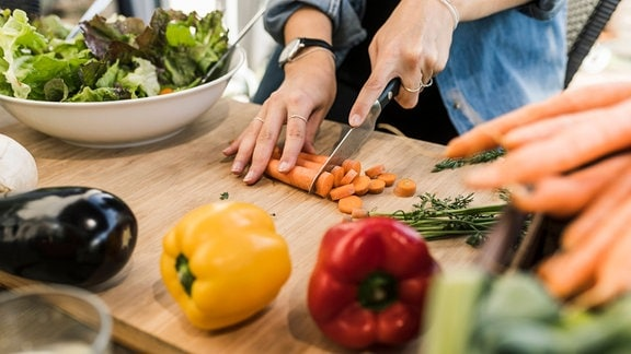 Auf einem Brett werden Möhren klein geschnitten, daneben Salat in einer Schüssel und anderes Gemüse
