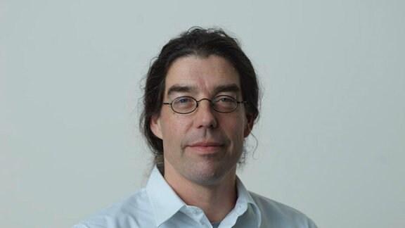 Dr. Hauke Walter, Labormediziner aus Stendal, Brille, weißes Hemd, lange dunkle Haare zum Pferdeschwanz gebunden, steht vor einer weißen Wand.