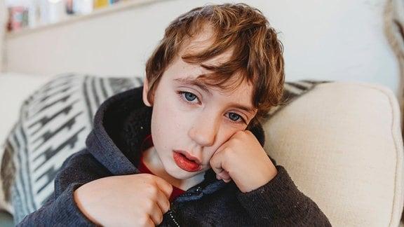 Ein Kind, das sich unwohl fühlt, schaut in die Kamera.
