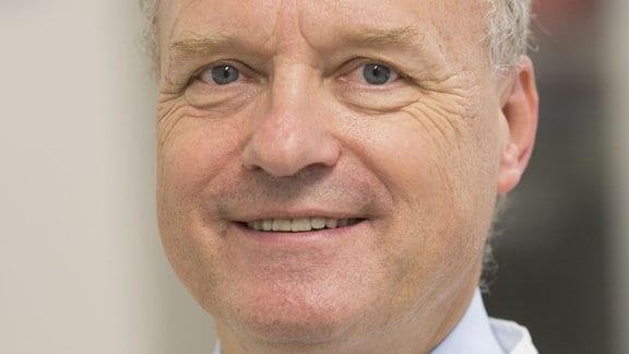 Prof. Dr. Reinhard Henschler vom Institut für Transfusionsmedizin in Leipzig schaut in die Kamera. Ein Mann mit weißen Haaren, weißem Kittel, lächelt leicht.