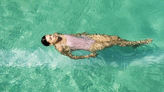 Eine junge Frau schwimmt in einem Pool auf dem Rücken