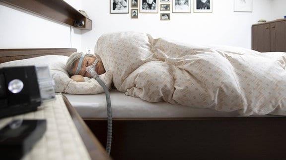 Frau schlaeft mit einem Luftbefeuchter bei Schlafapnoe
