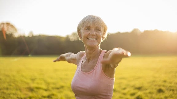 Lächelnde Seniorin macht Yoga