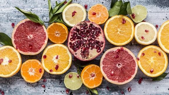 Verschiedene aufgeschnittene Zitrusfrüchte und Granatapfel