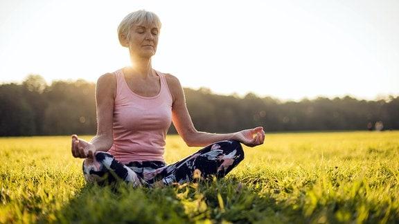 Eine Frau meditiert in einem Park