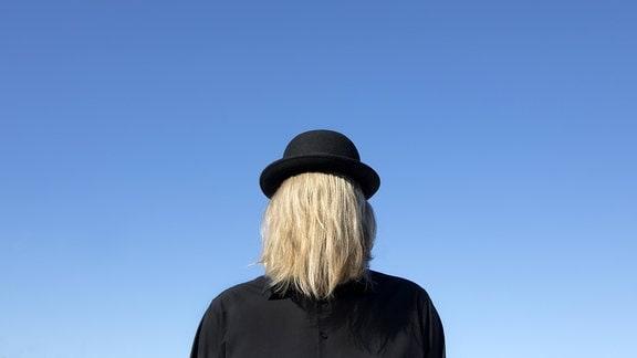 Ein Mann mit Anzug und Bowler hat seine langen blonden Haare vors Gesicht gekämmt.