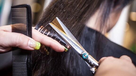Eine Friseurin beim schneiden von aufgespaltenen Haaren (Spliss)
