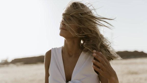 Frau mit langen vors Gesicht gewehten Haaren